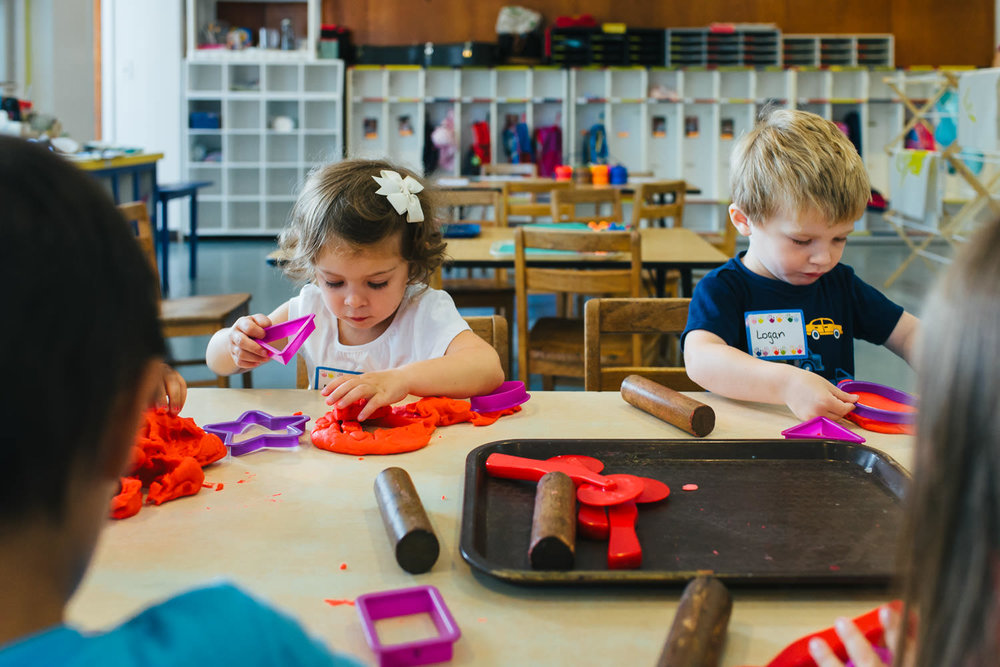 Children play with play doh at preschool.