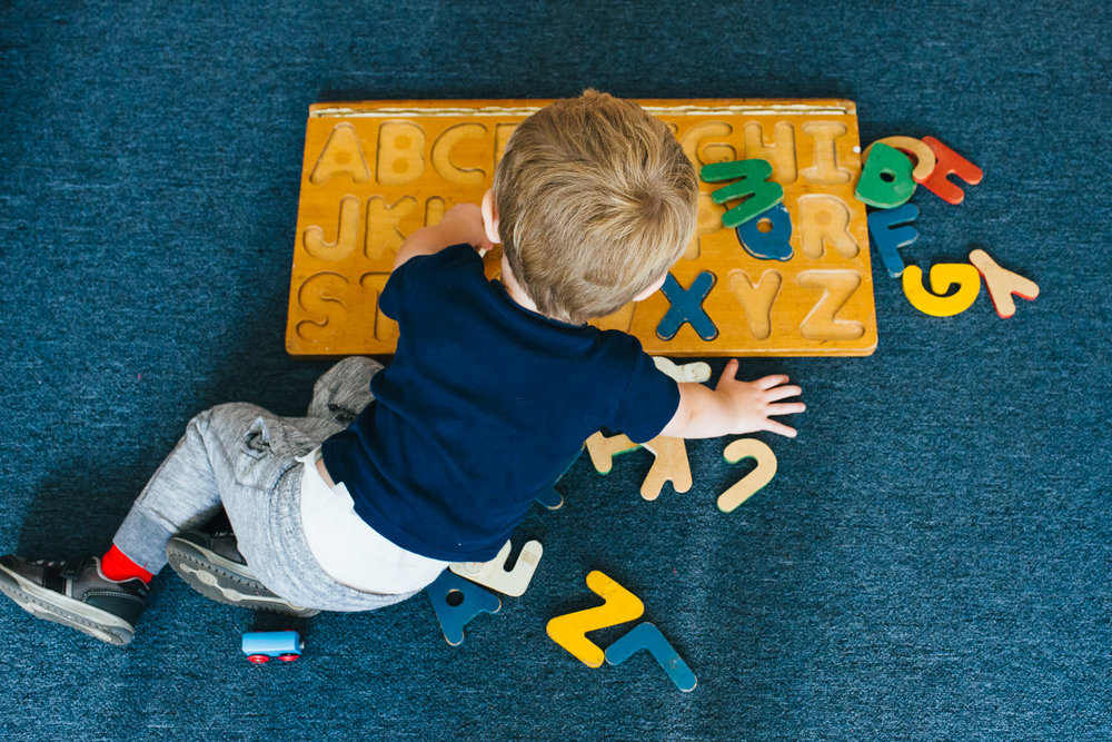 A little boy plays with an alphabet puzzle.