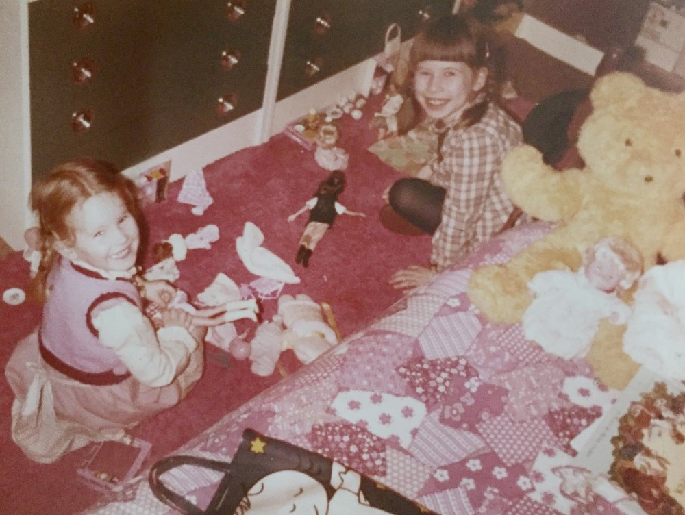 Two girls play with dolls in their bedroom in the 1970's.