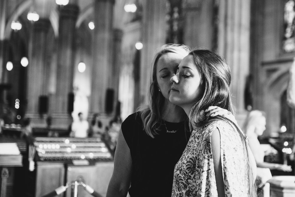 A mother and daughter embrace in St. Patrick's Cathedral.