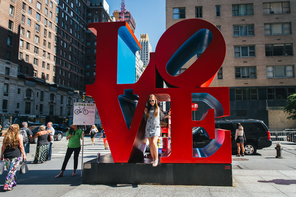 "A woman poses for a picture with the ""Love"" sign in NYC."
