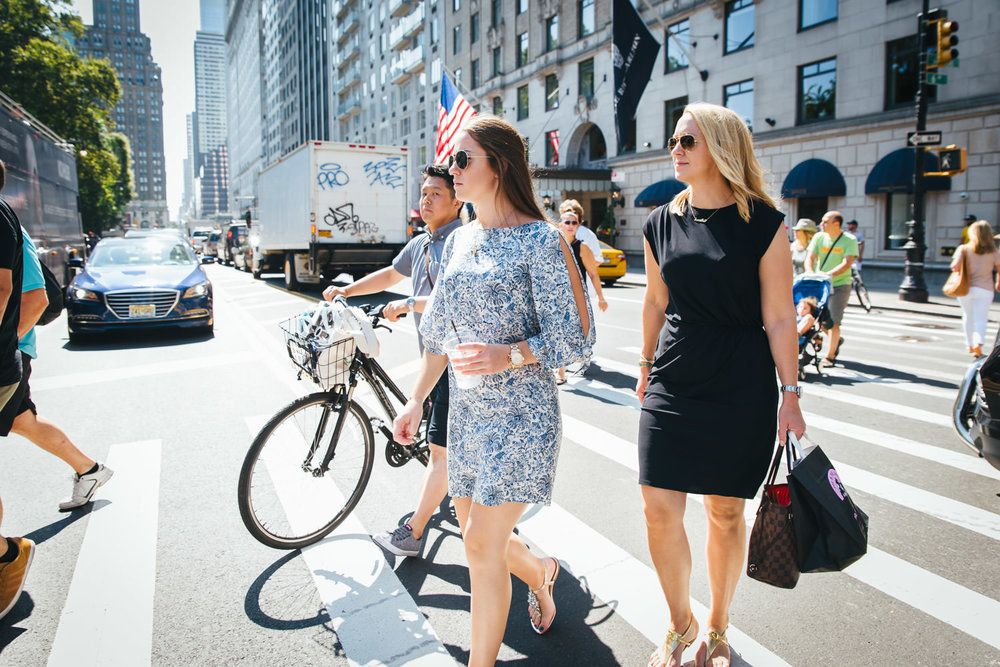 A mother and daughter cross 59th Street to Central Park.