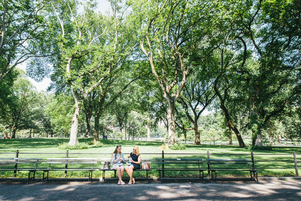 A mother and daughter sit on a bench in Central Park.