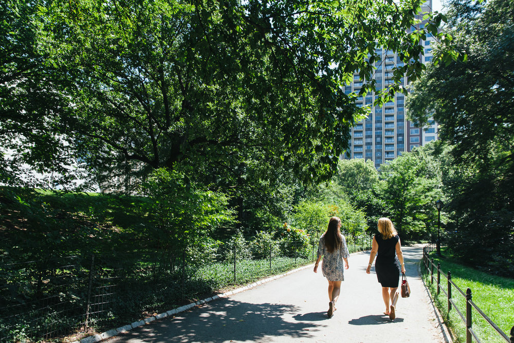 A mother and daughter walk down a path in Central Park.