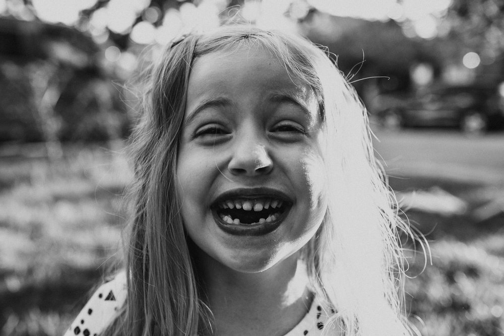 A portrait of a young girl missing her two front teeth.