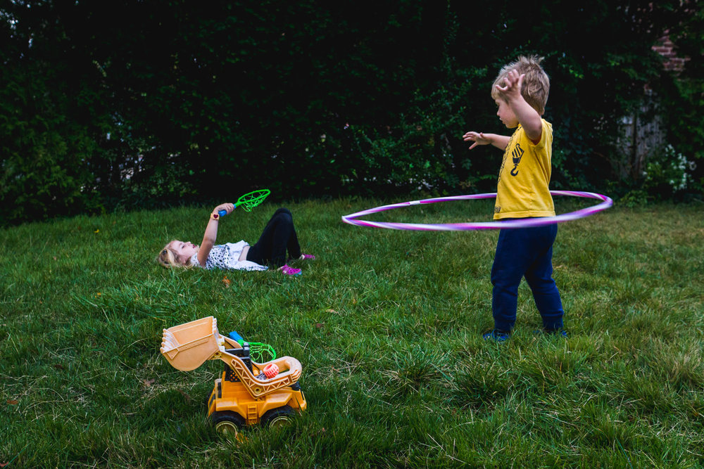 Two kids play on their front lawn with a hula hoop and a tennis set.