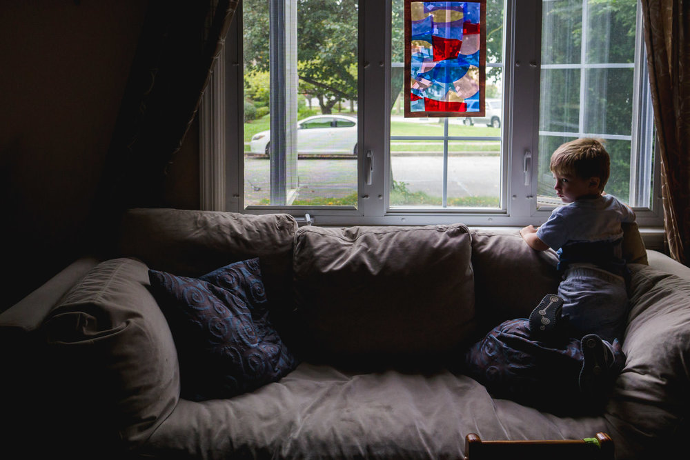 A little boy looks out the window from his couch.