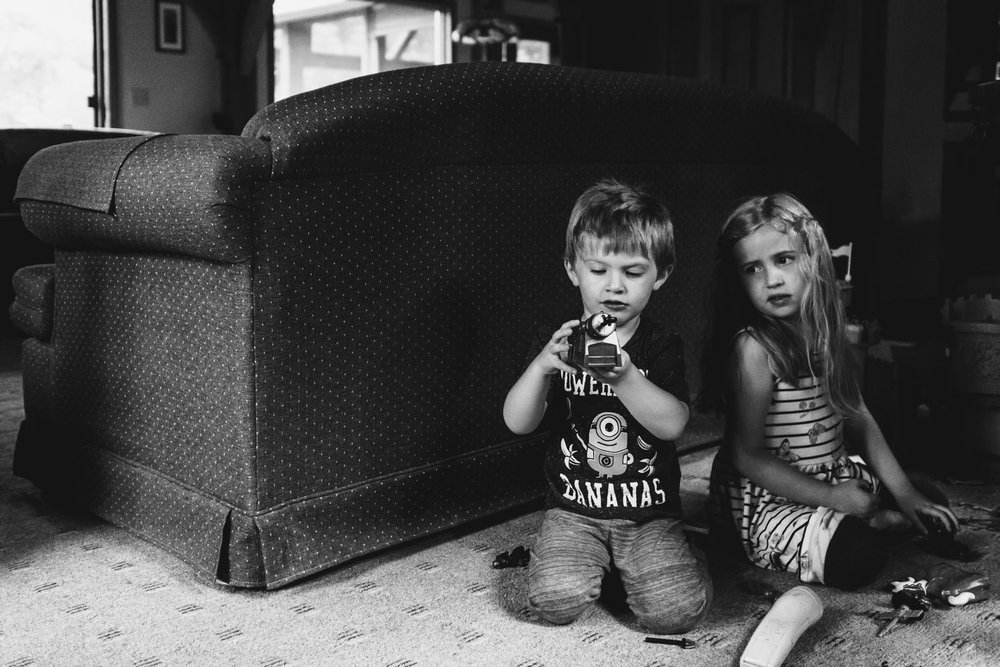 A brother and sister play with action figures behind a couch.