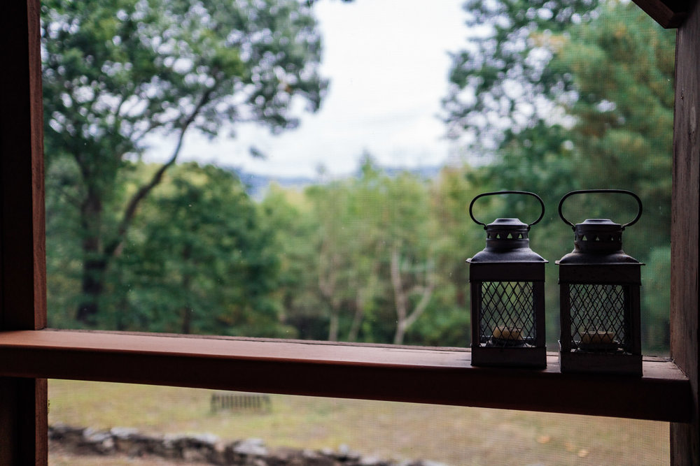 Two lanterns sit on the railing of a porch.