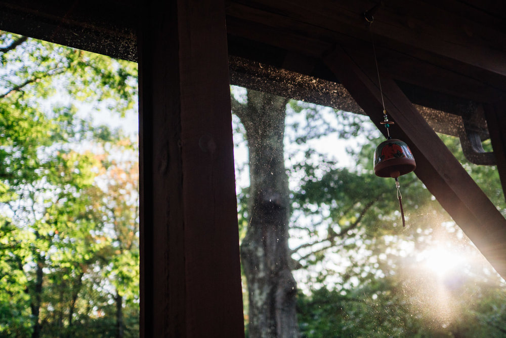 A wind chime blows on a porch.