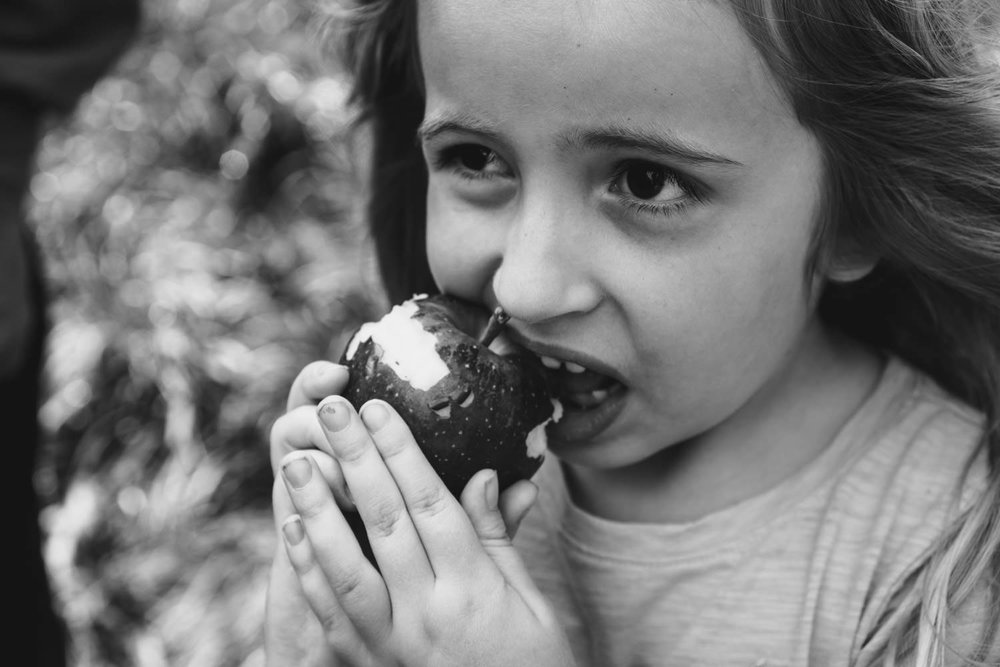 A little girl takes a bite out of an apple.