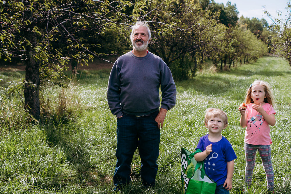 Two kids and their grandfather watch as someone picks apples at an orchard.