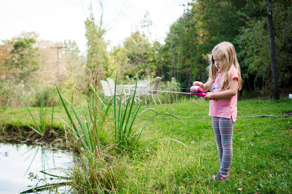 A little girl fishes by the bank of a pond.