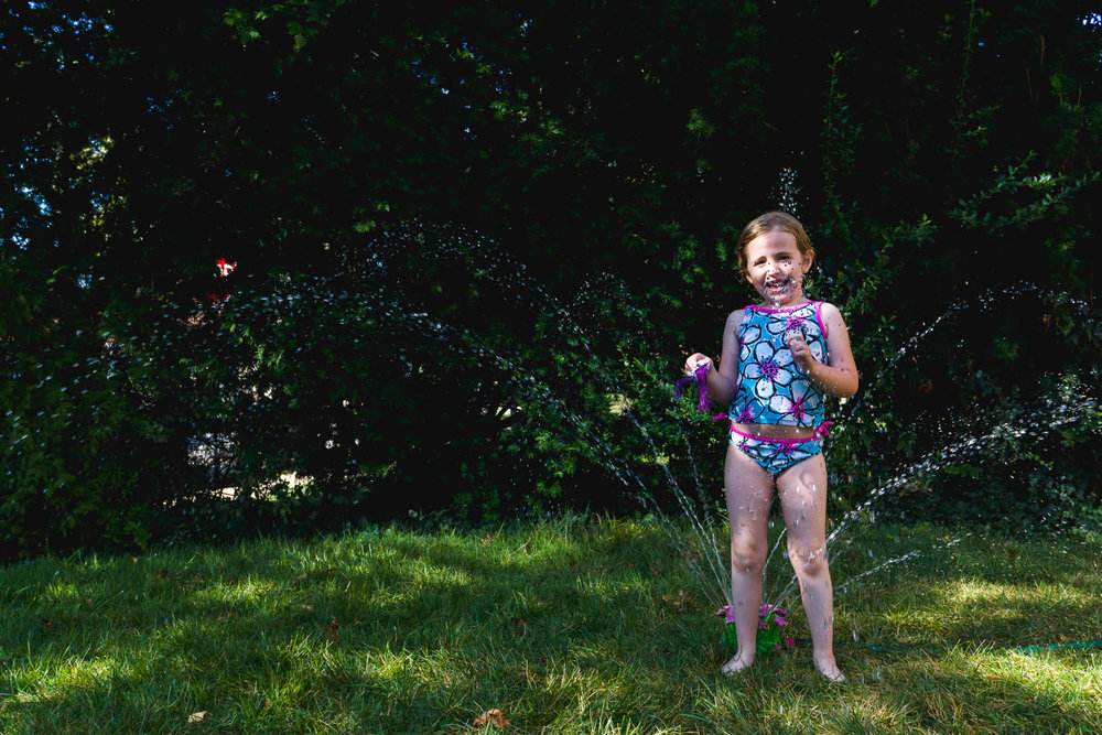 A little girl plays in a sprinkler in her front yard.