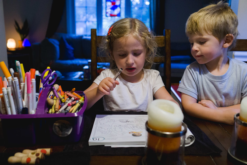 Two kids sit at the table and do their homework.