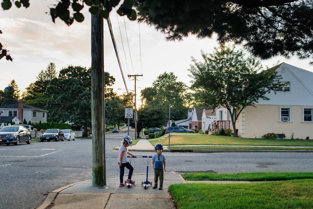 Two kids riding scooters stop at a corner.