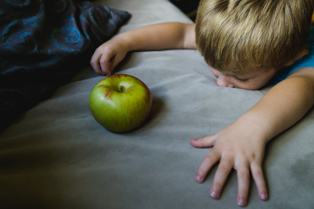 A little boy plays with an apple on the couch.