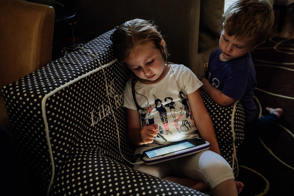 A brother and sister play with a Leappad in their living room.