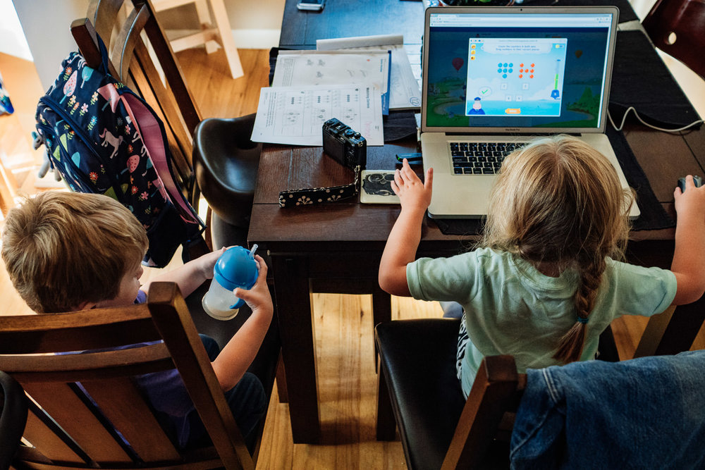 Two kids play a computer game at their kitchen table.