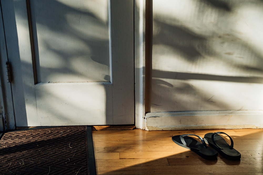 Flip flops on the floor by a closet in pretty light.