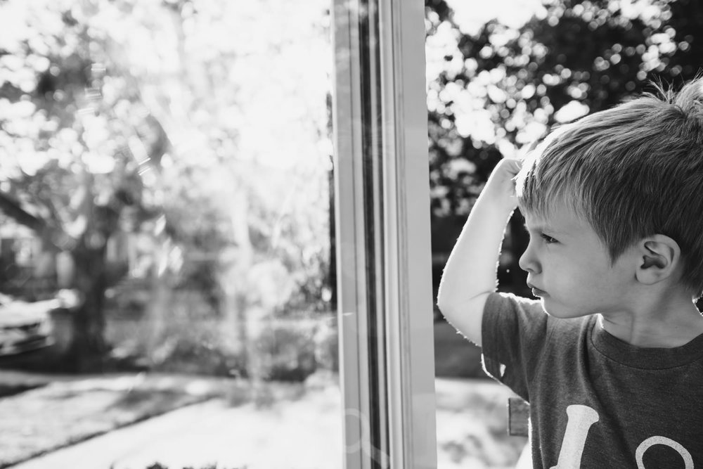 A portrait of a little boy next to his storm door.