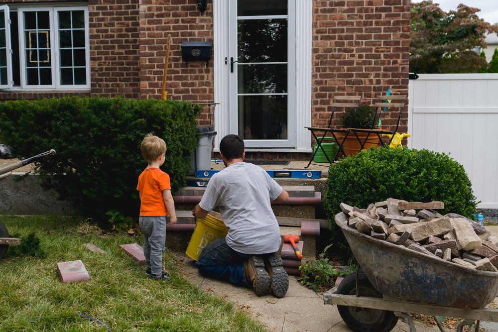 A little boy watches while his dad does some masonry work on the front porch.