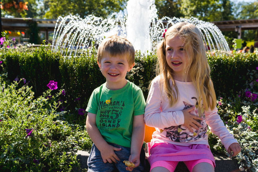 Two kids smile in front of the fountain at Hicks Nursery.