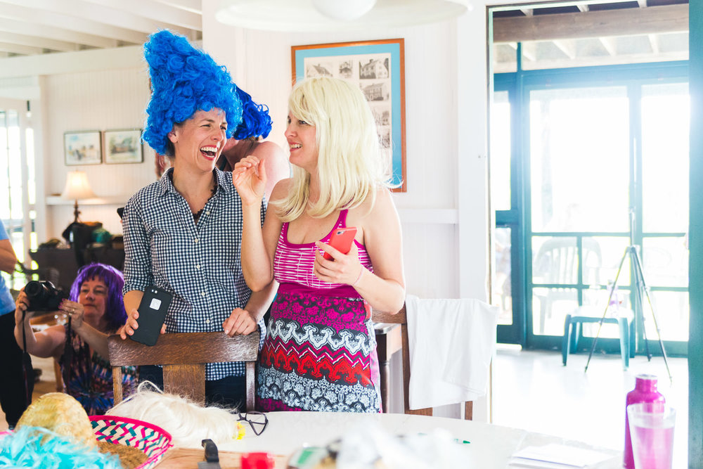 Women in wigs laugh at a retreat weekend.