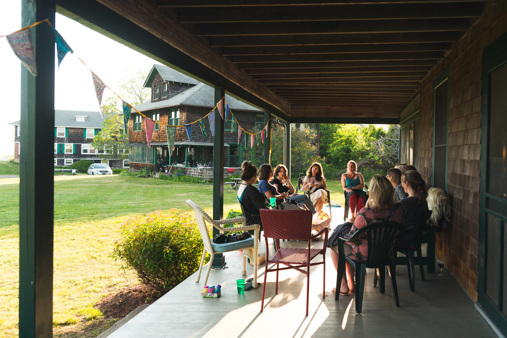 Women gather on a porch at a retreat weekend.