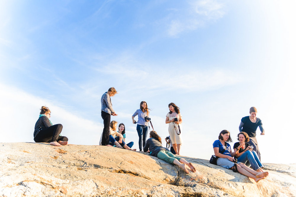 Woman congregate on top of some rocks by the beach.