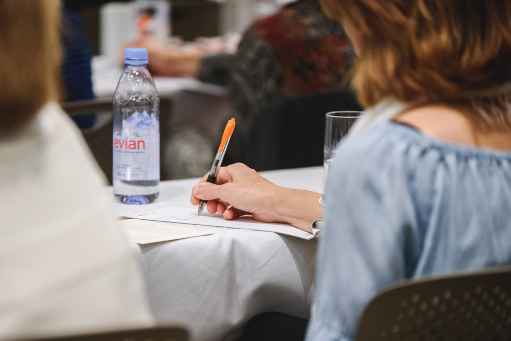A woman jots down notes at an event.