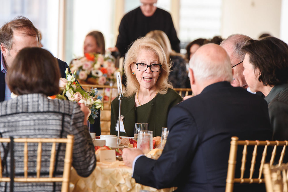People chat at an event luncheon.