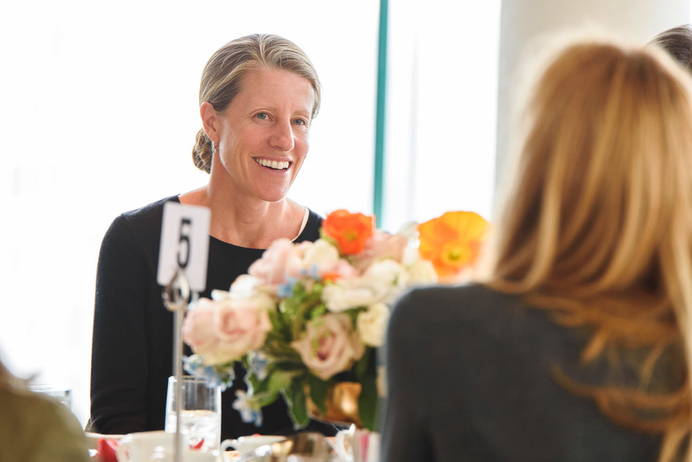Women chat over an event lunch.