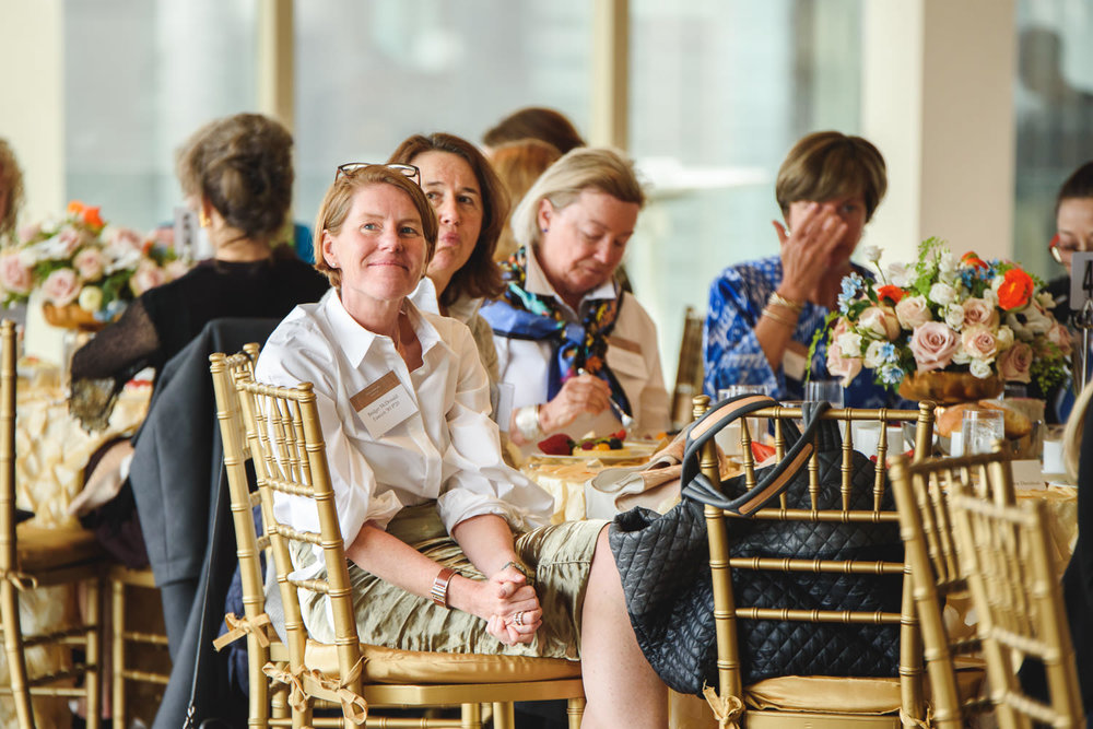 Women listen to speakers at a luncheon.