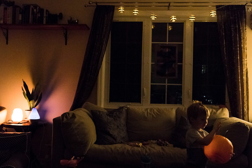 A little boy carries a plastic pumpkin in a dark living room.