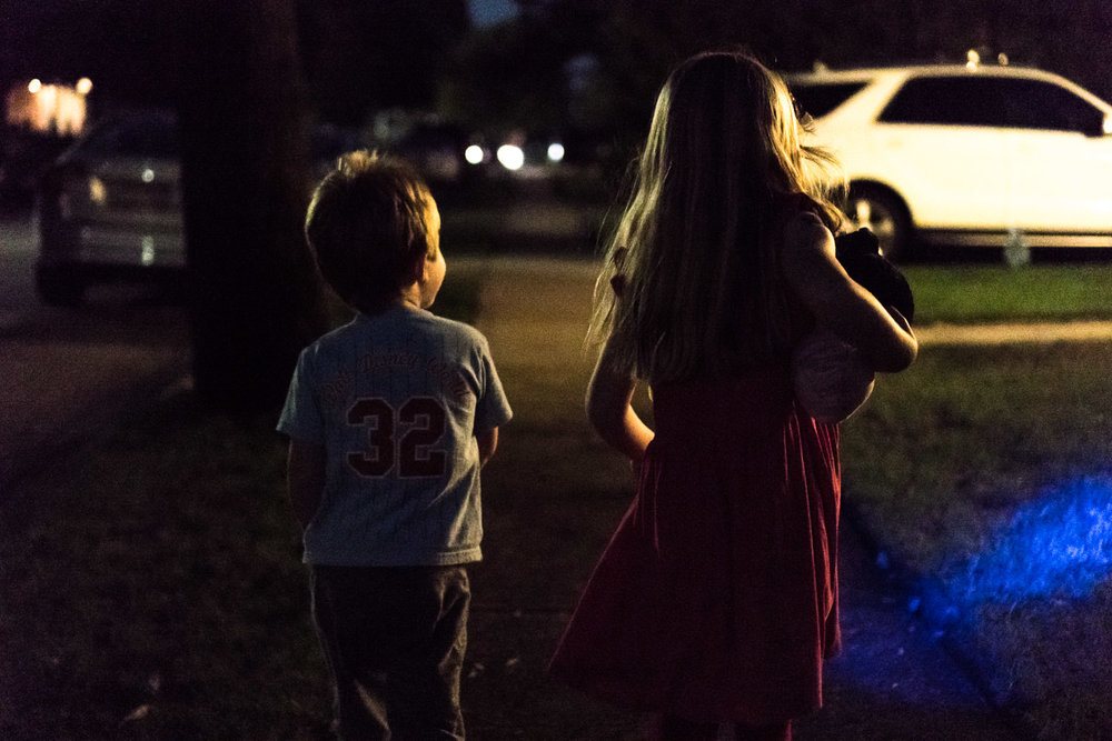 Two children on a walk in the dark.