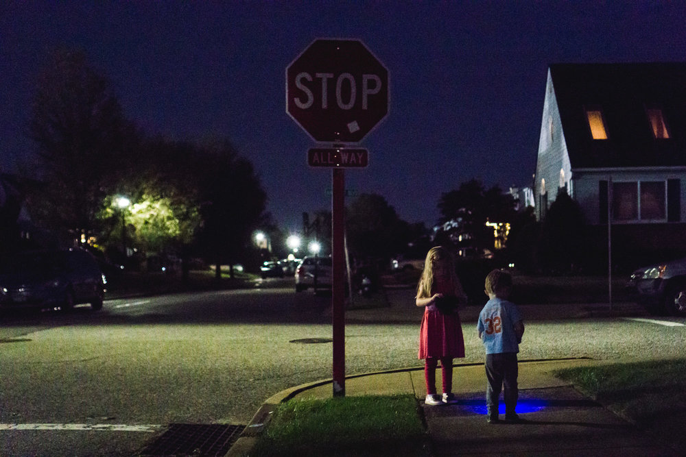 Two children wait with flashlights on a street corner.