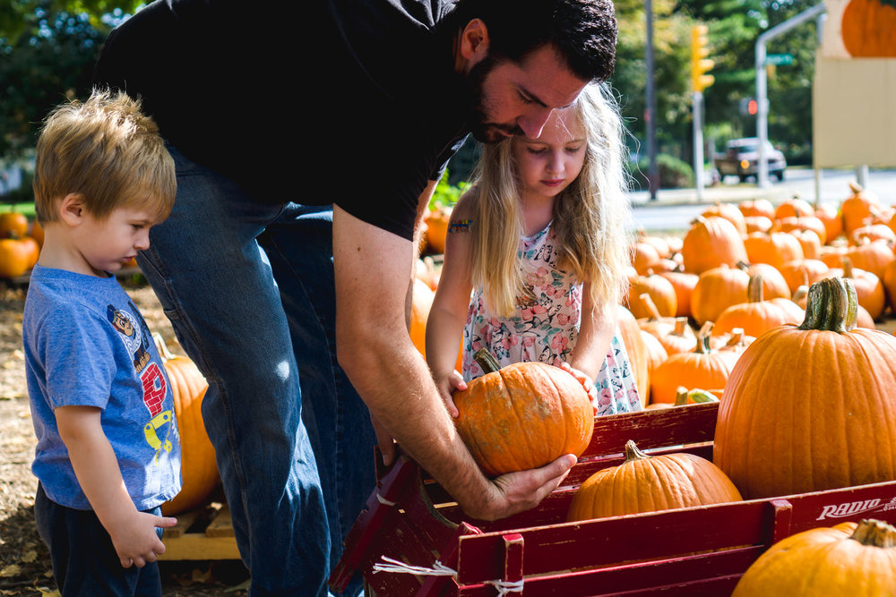 A father helps his young kids load pumpkins into a wagon.