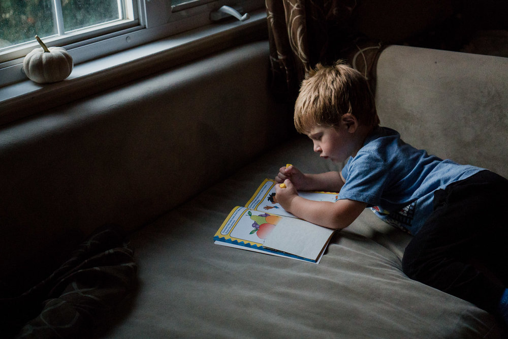 A little boy works on an activity book on the couch.