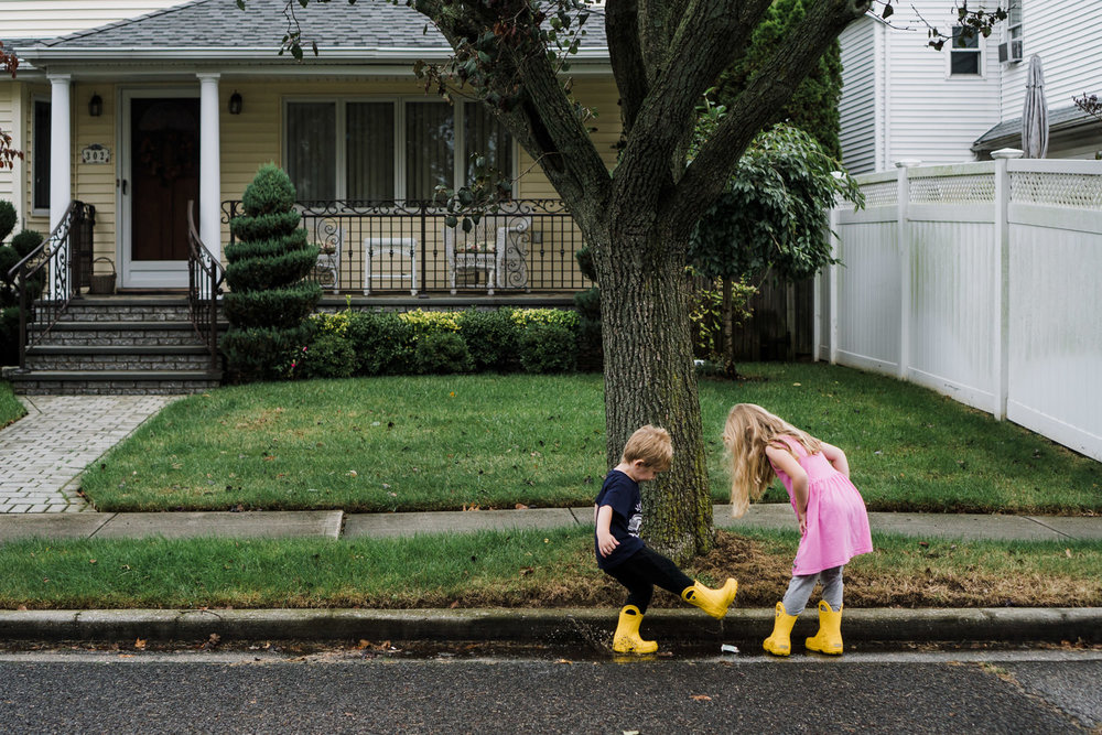 Two kids wearing yellow boots splash in puddles outside a house.