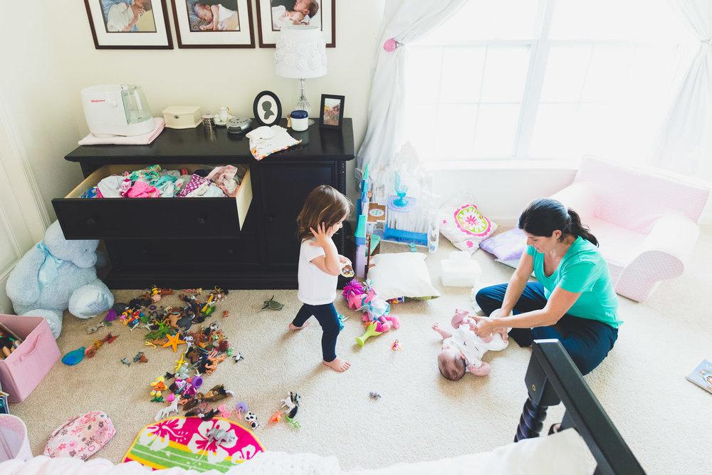 A mom changes her baby's diaper on the kids' bedroom floor.