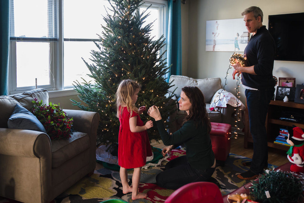 A family decorates the Christmas tree.