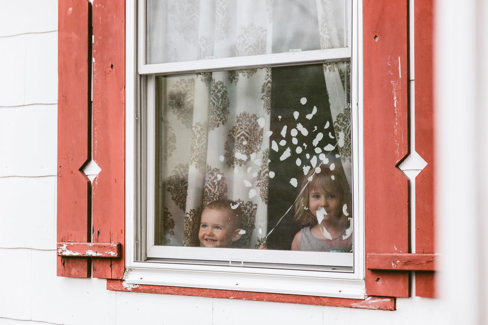 Children peer out their front window.