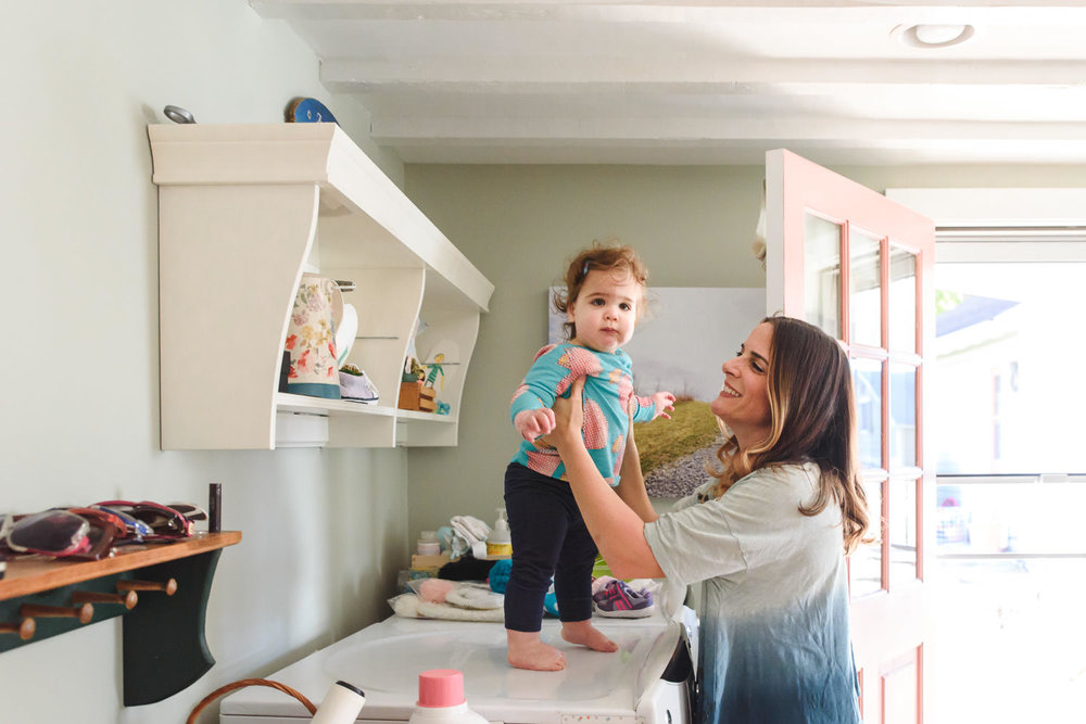 A mother smiles at her daughter who is standing on the dryer.