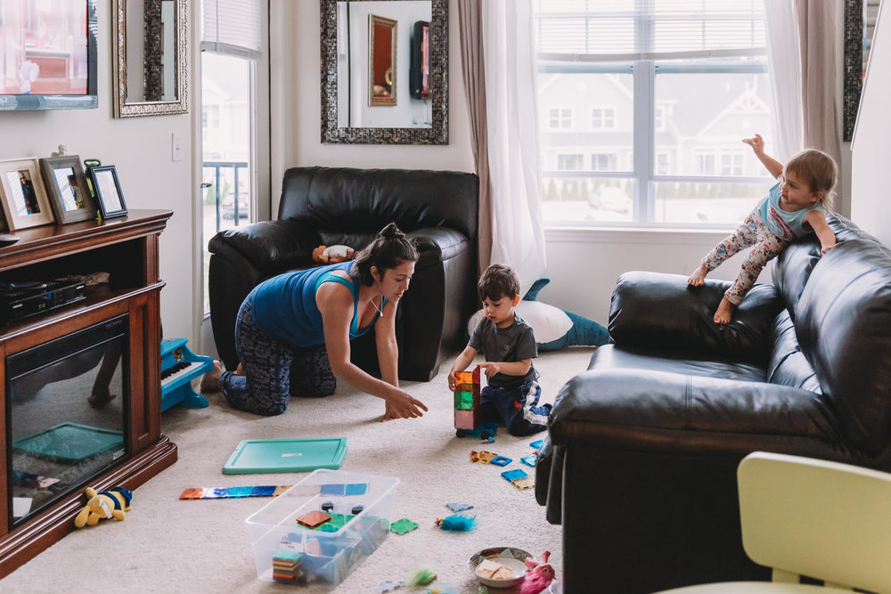 A mother plays with her kids in the living room.