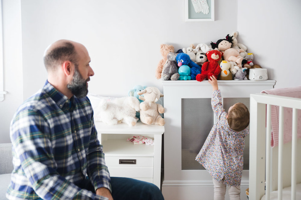 A little girl reaches for a stuffed animal in her bedroom.