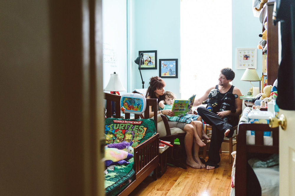 Parents read their toddler son a book.