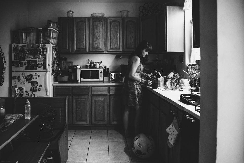 A mother prepares milk in her kitchen.