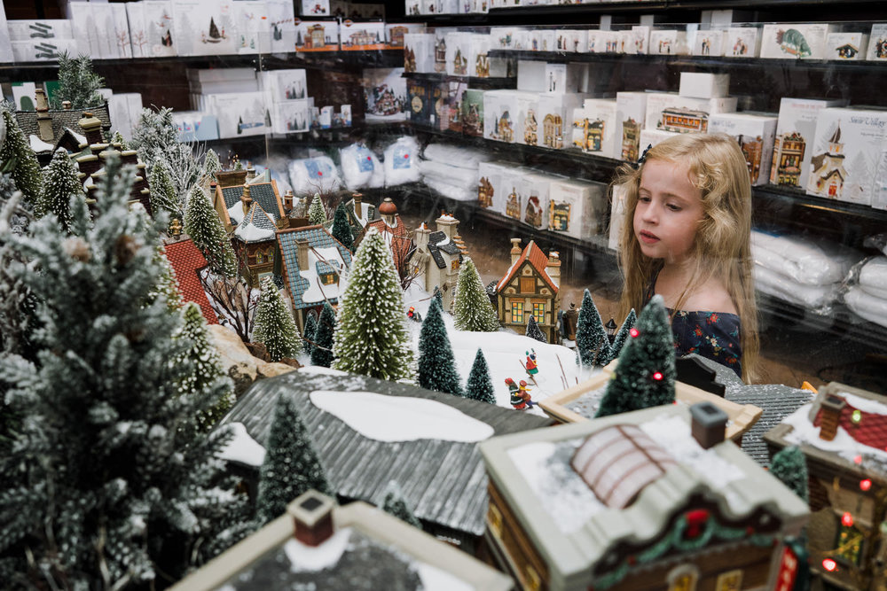 A little girl looks at a holiday village display.