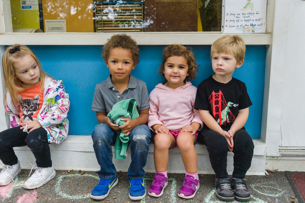 Preschoolers sit along the wall outside their classroom.